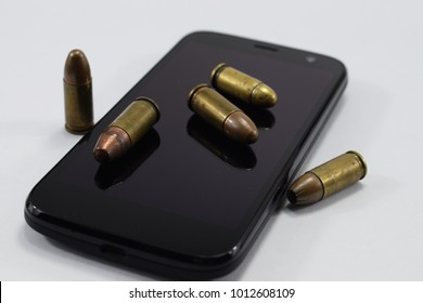 fighting bullets for a pistol, different cartridges and a cellphone on a white background