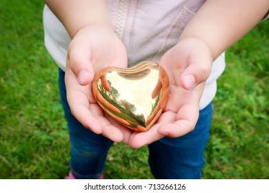 Fighting heart disease. Girl holding a golden heart.