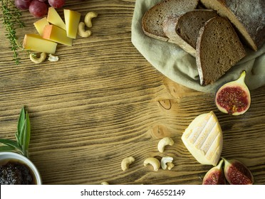 figs, bread and cheese on wooden Table  with salsa and nuts