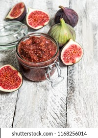 Figs marmalade in jar. Fruit jam on rustic wooden background. Preserving ingredients