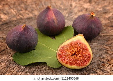 Figs and one fig sliced in half on old wooden background. Focus is on the sliced fig.