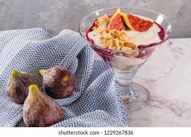 Figs pudding parfait with yogurt, blueberry jam, figs, hazelnut, and cookies in glass on white marble background.