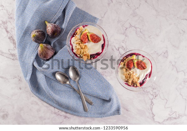 Figs pudding parfait with yogurt, blueberry jam, figs, hazelnut, and cookies in glass on white marble background. Flatlay top view.