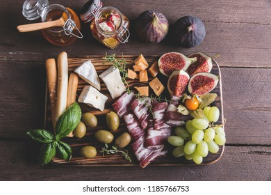 figs,camembert cheese,prosciutto ,olives, grapes on dark serving board over rustic wooden background.Top view