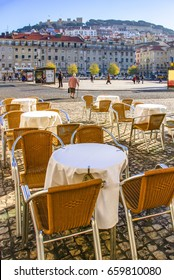 Figueira Square in Lisbon with a set of coffee-shop tables in a terrace in the foreground