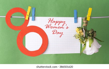 figure 8, paper flowers hang on clothespins in front of green background. International Women's Day. March 8, Happy Women's Day greeting message text