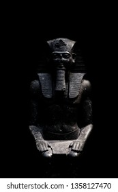 Figure allusive to Pharaoh, isolated on black background seen from front.