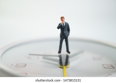 Figure businessmen are thinking And standing on the white watch face by the watch face showing the time. Concept of time management.
