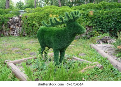 Figure of deer made of green lawn grass in the park, free space. Green grass covered topiary deer, landscape design. Grass figure of deer, topiary figure