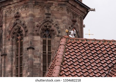 figure of the Deutscher Michel with a beer in his hand sleepwalking on a roof and red tiles
