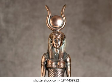 The figure of the Egyptian goddess Isis on a brown corduroy background. Bronze statuette.