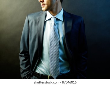 Figure of elegant businessman in suit posing in darkness