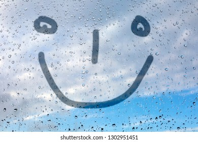 Figure emoticon on the misted glass. Glass window with raindrops against the blue sky. Emitation of children's drawings.