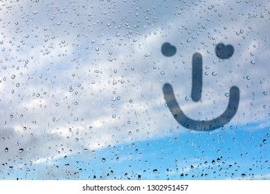 Figure emoticon on the misted glass. Glass window with raindrops against the blue sky. Emitation of children's drawings. Place for inscription.