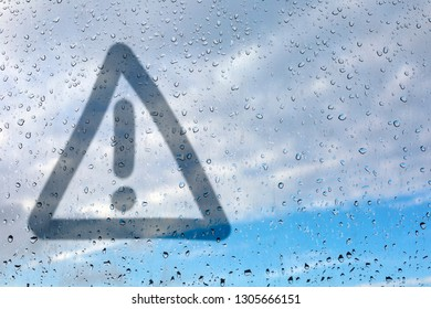 Figure exclamation point in a triangle on misted glass. Glass window with raindrops against the blue sky. Place for inscription. Caution danger