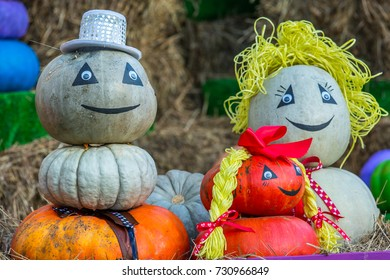 The figure of a family from mom, dad and daughter with braids, assembled from pumpkins, is located in the street around the sheaves of hay. Colorful autumn in Moscow city, Russia.