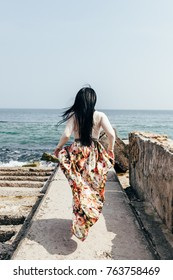 a figure of the girl from the back in full growth with dark long straight hair with a skirt with flowers on the beach in the sea