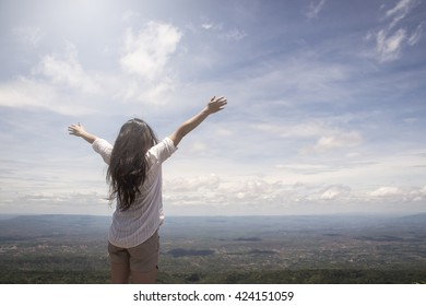 Figure of a girl from the back raising her hands joyfully to celebrate freedom with clouds and vast landscape as background and intentional sun flare effect
