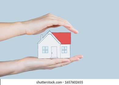 The figure of a house in human hands. Hands hold and gently cover a figure of home - concept of home insurance, safety, family planning, mortgage and safe house