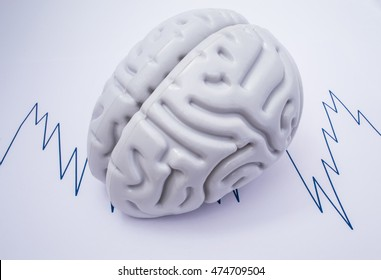 The figure of the human brain lies on sheet of paper, where the drawn curve recorded electroencephalogram (EEG). Illustration or picture of neuronal brain activity to use in neurology and neuroscience