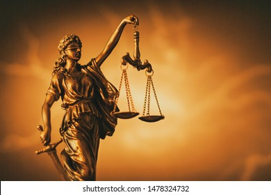 Figure of Justice with sword and scales over a gradient brown background with central highlight and copy space in a conceptual image