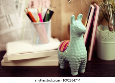 Figure of llama on a work table with books and pencils, back to school concept