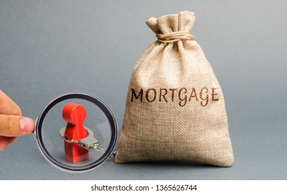 The figure of a man is handcuffed to a money bag with the word Mortgage. Impossibility of paying interest rates on mortgages and repayment of loans. Debt load. Ban debtors from leaving the country.