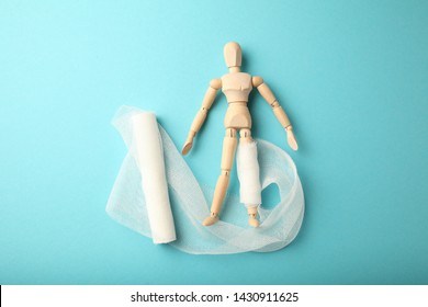 Figure of man with leg wound and white gauze bandage. First aid, injury treatment. Patient in hospital.