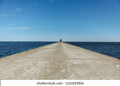 Figure of a man walking on a pier in Nida, Lithuania