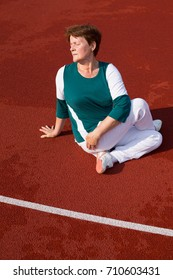 Figure of mature beautiful woman in spine twisting yoga position, at the stadium, outdoors. Healthy fitness lifestyle.