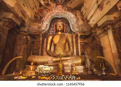 Figure of meditating Buddha inside cave of stone temple. Buddhist structure with sculptures from 14th century, Sri Lanka.