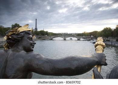 Figure on the Alexandre III Bridge looking towards the Eiffel Tower, Paris, France