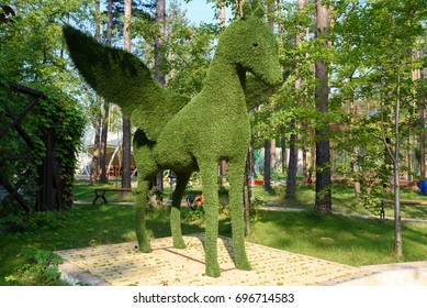 Figure of pegasus made of green lawn grass in the park, free space. Green grass covered topiary pegasus, landscape design. Grass figure of pegasus, topiary figure