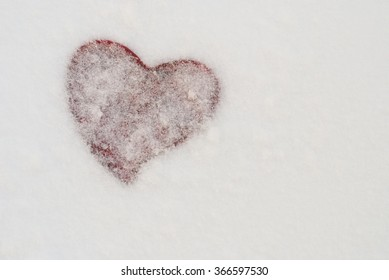 figure of a red heart on the background of snow