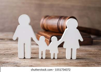 Figure in shape of people and gavel on wooden table. Family law concept