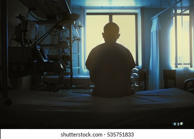 Figure of sitting patient on a hospital bed on the background of bright lights