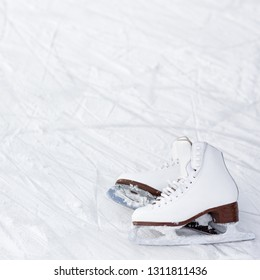 figure skates and copy space over ice background with marks from skating