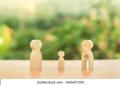 Child's figure stands between father and mother. The child chooses which parent to live with after their divorce. Guardianship over child. Taking into account the interest of child, payment of alimony