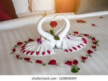 figure of swans made out of towels on the bed. bed decoration with flowers and rose petals, romantic interior