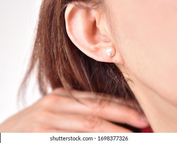 A figure that pulls hair back by hand. A pearl earring in the ear.