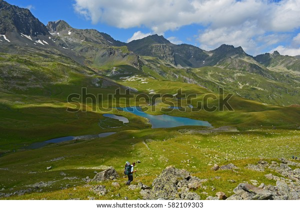 A figure of a tourist on the background of mountains and blue lake