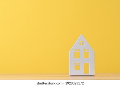 Figure of toy house on yellow background with copy space