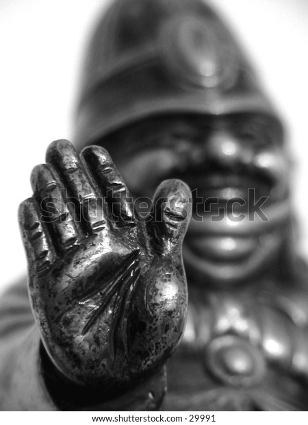 Figure of traffic policeman with hand raised to stop traffic.