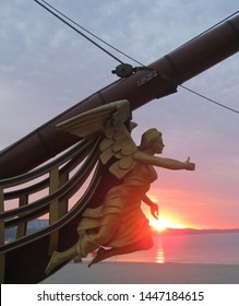 Figurehead (nose shape) is an ornament on nose of sailboat. Wooden sculpture of woman.