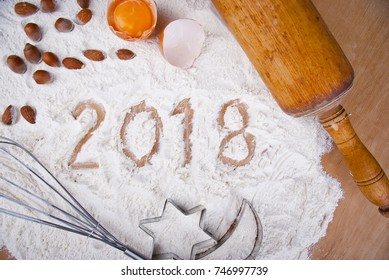 Figures 2018 written in flour on kitchen table with raw egg, nuts, whisk, casts and rolling pin, concept.