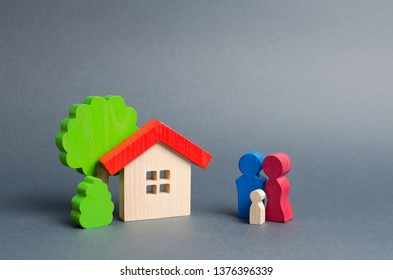 Figures of the family and house on a gray background. real estate, your own home. Affordable housing on credit or mortgage. Renovation and construction. Subsidies, citizenship.