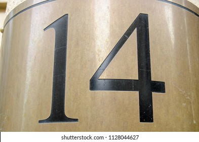 Figures for the number 14 incised into a curved brass plate outside an office block in central London. Viewed from public pavement.