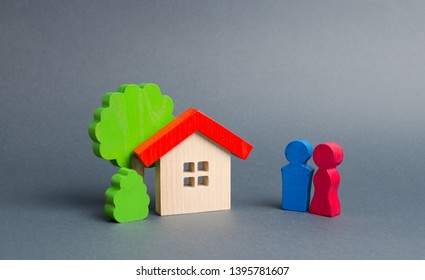 Figures of the young couple and house on an gray background. real estate, your own home. Affordable housing on credit or mortgage. Renovation and construction. Subsidies, citizenship.
