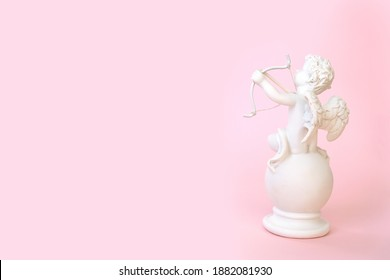 figurine of an angel Cupid with a bow on a pink background. Valentine's Day.