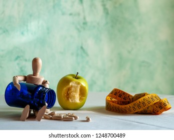 A figurine with a bitten apple, a tape measure and a blue container with vegetable fiber pills on a table